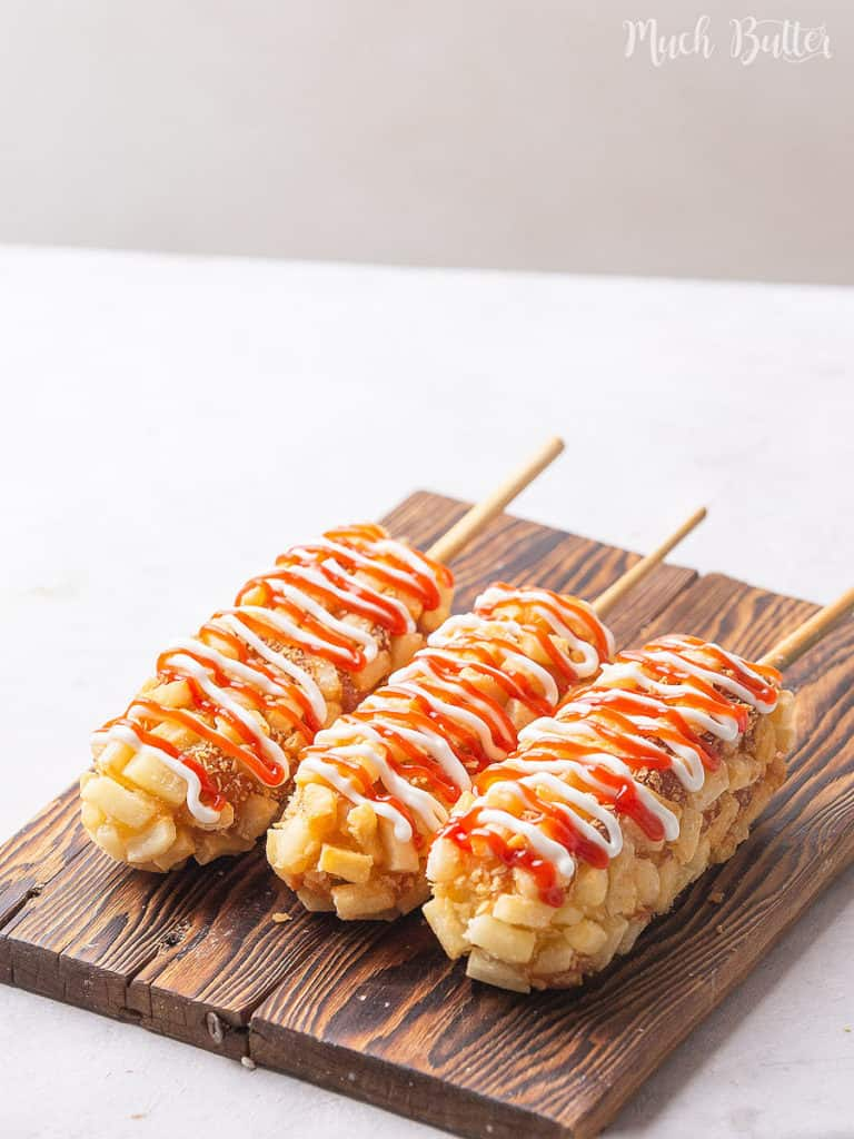 Coddling your movie time with Korean Corn Dog! It is mozzarella or sausage coated with diced french fries and panko breadcrumbs. Using the deep-fried method, this snack will be cheesy, crunchy, and tasty.
